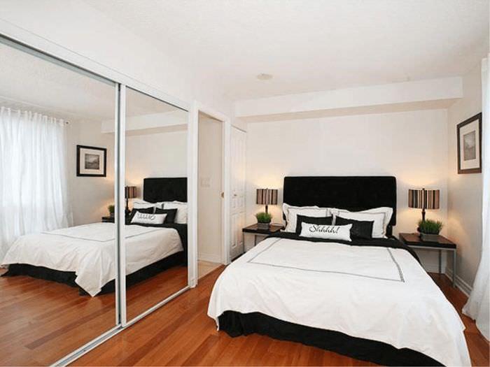 Большие зеркала на стене узкой спальни