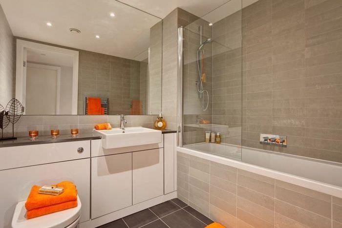 Оранжевое полотенце в ванной комнате с большим зеркалом