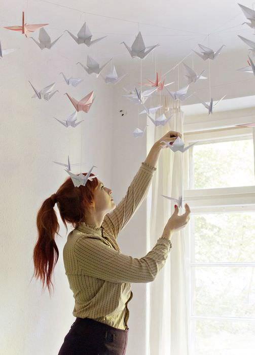 Мама вешает бумажные фигурки журавликов на потолок комнаты