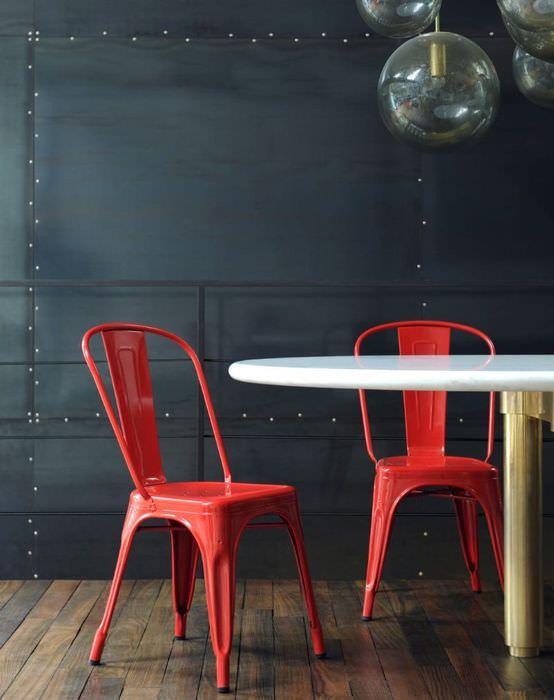 Два красных стула на фоне черной стены