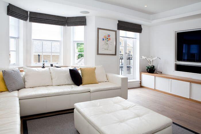 Интерьер белой гостиной с черными римскими шторами