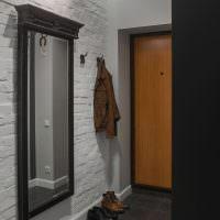 Зеркало в черной рамке на белой стене