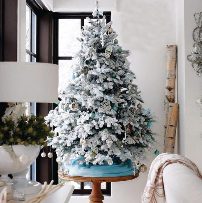Небольшая новогодняя елка на круглом столике из дерева