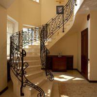 Лестница с кованными перилами в коридоре загородного дома