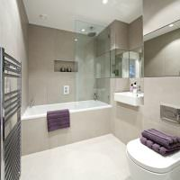 Сиреневое полотенце на бортике акриловой ванны