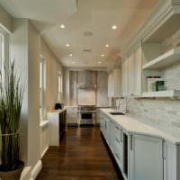 Два ряда точечных светильников на потолке узкой кухни