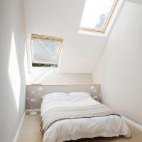 Интерьер белой спальни в мансардном помещении