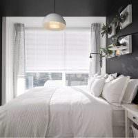 Белая кровать в комнате с серыми стенами
