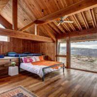 Спальня с панорамным окном в доме из бруса