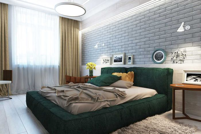 Темно-зеленая кровать в спальне с кирпичной стеной