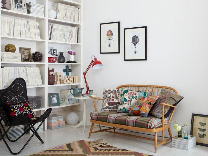 Деревянная кушетка с пестрыми подушками у белой стены