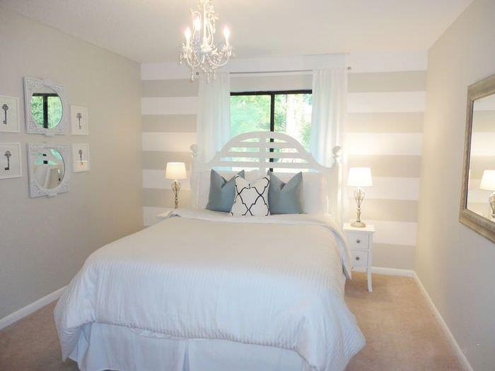Маленькая кровать в комнате с окном в торце
