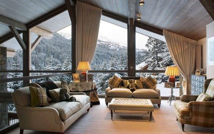 Интерьер просторной гостиной в мансарде частного дома