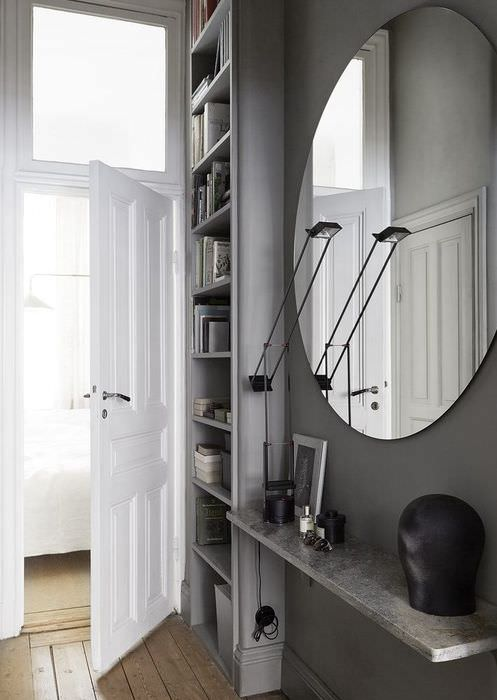 Овальное зеркало на серой стене прихожей