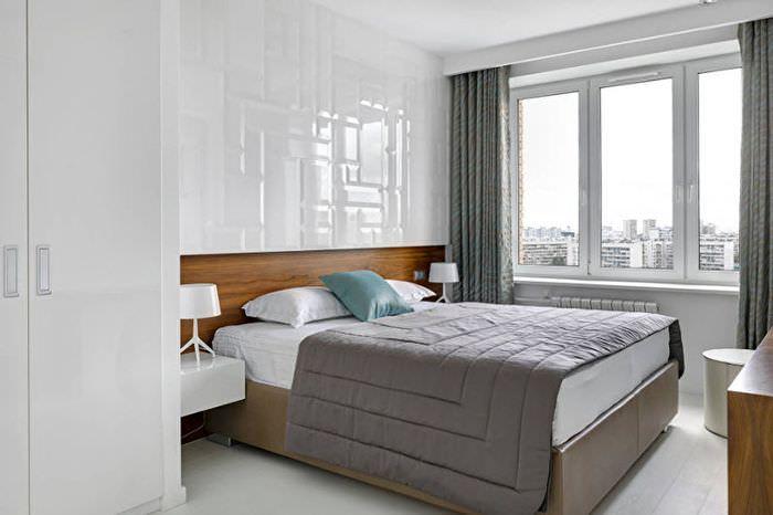 Серое покрывало на кровати в спальне