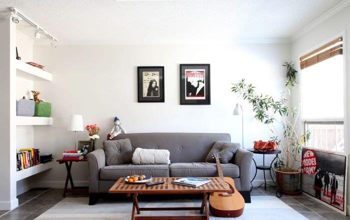 Серый диван на фоне белой стены гостиной