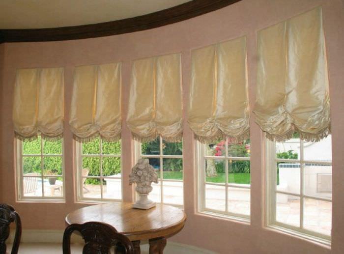 Бежевые австрийские шторы на узких окнах эркера в частном доме
