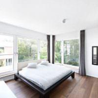 Интерьер светлой спальни с панорамными окнами