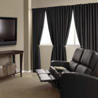 Черные шторы в комнате с массажным креслом