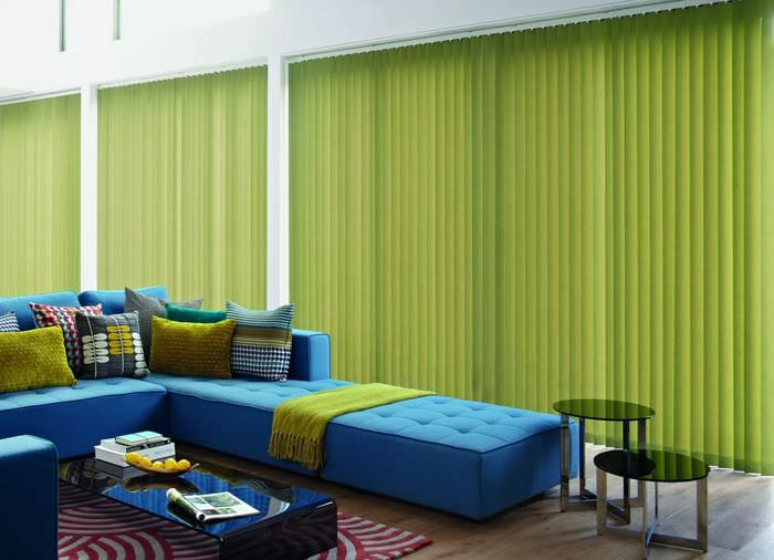 Синий диван в гостиной с зелеными шторами