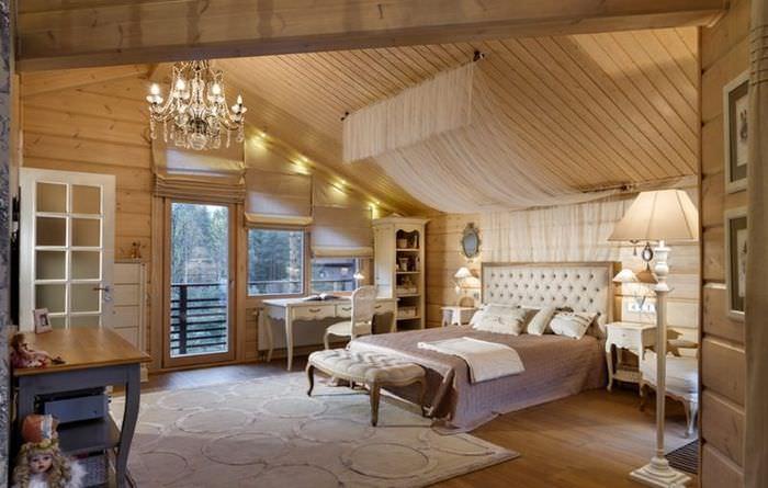 Интерьер спальни в мансарде дома из бруса