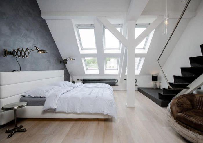 Несколько небольших мансардных окон в спальне стиля лофт