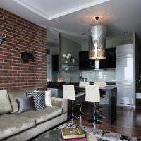 Серый диван вдоль кирпичной стены