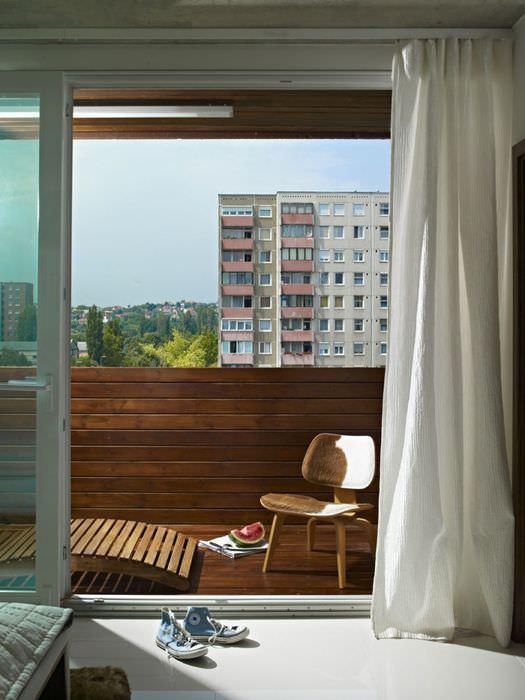 Небольшой стульчик на балконе в трехкомнатной квартире