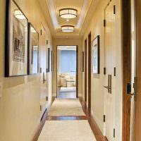 Светлые коврики на коричневом полу коридора