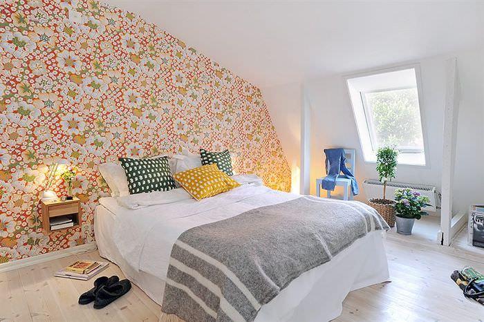 Пестрые обои на стене спальни в мансарде