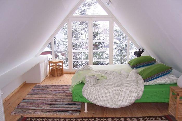 Зеленая кровать в спальне на мансарде