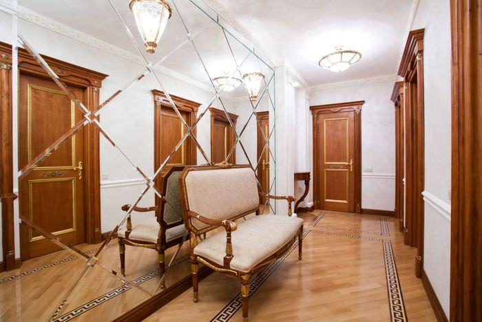 Коричневые двери в узком коридоре с зеркальной стеной