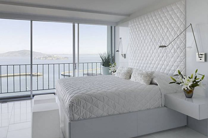 Белая кровать в спальне с панорамным окном