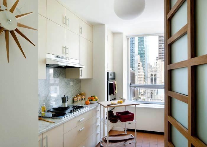 Открытая дверь в белую кухню линейной планировки
