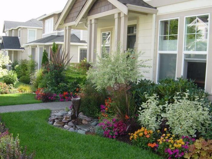 Клумба с многолетними растениями перед крыльцом дачного дома