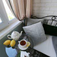 Небольшой стеклянный столик на балконе