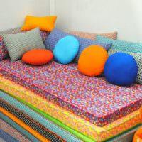 Яркие подушки из разноцветного материала для декора дивана