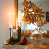 Веточки с сухими листьями березы в вазе на комоде