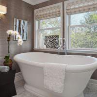 Белая ванна в комнате с серыми стенами