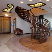 Винтовая лестница из дерева в холле частного дома