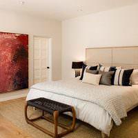 Дизайнерский пуф перед кроватью в белой спальне