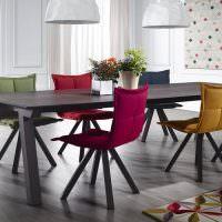 Мягкие стулья разного цвета в столовой-кухне частного дома