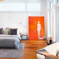 Оранжевая картина на полу спальни