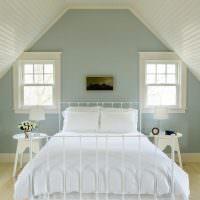 Белая кровать в мансарде загородного дома