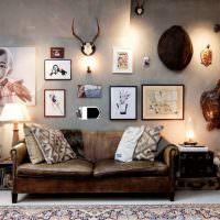 Старый диван возле серой стены с фотографиями