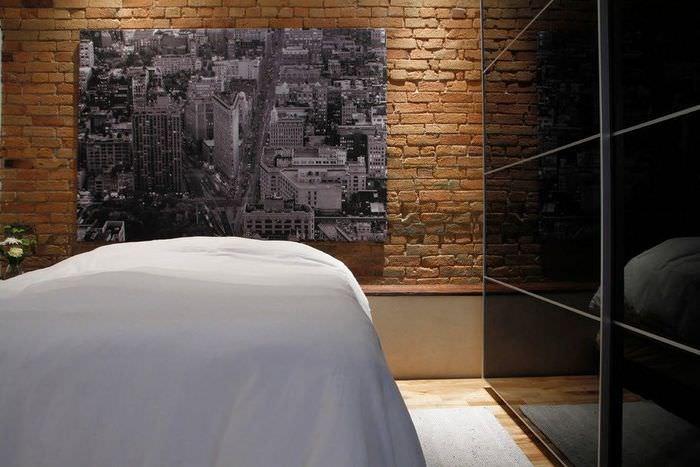 Фотообои с темой ночного города на кирпичной стене спальни