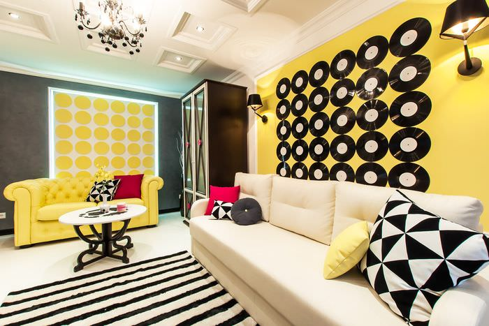 Виниловые пластинки на желтой стене гостиной в стиле поп-арт