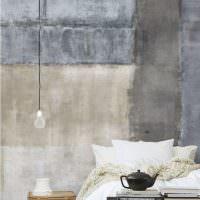 Белая кровать на фоне серой бетонной стены