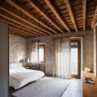 Деревянный потолок в спальне с каменными стенами