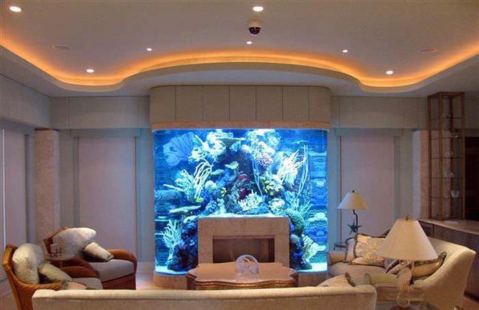 Камин с аквариумом в интерьере гостиной загородного дома